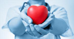 Доктор, който държи декоративно сърце в ръцете си