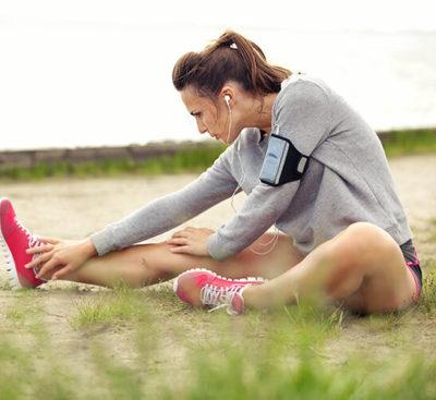 Млада жена, която се разтяга преди тренировка