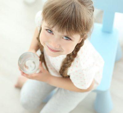 Малко момиче, което държи чаша вода