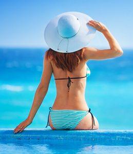 Младо момиче, което седи до басейн