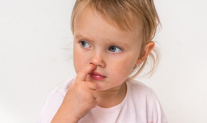 Малко момиче, което си бърка в носа