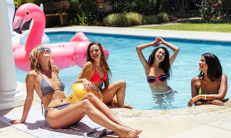 Момичета, които се забавляват до басейн