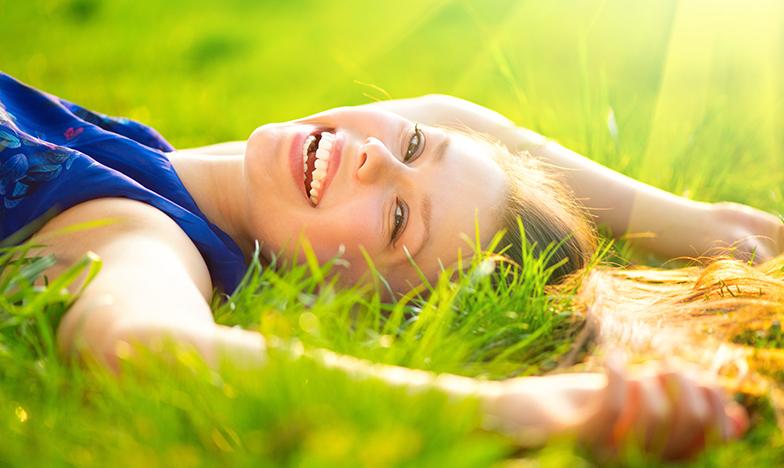 Усмихнато момиче, което лежи в трева