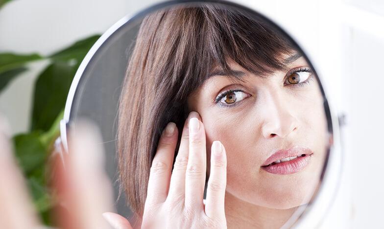 Жена, която се гледа в огледало