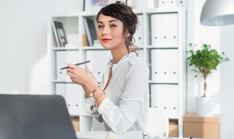 Момиче, което седи на бюрото си в офис
