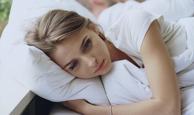 Момиче с бледо лице, което лежи в легло