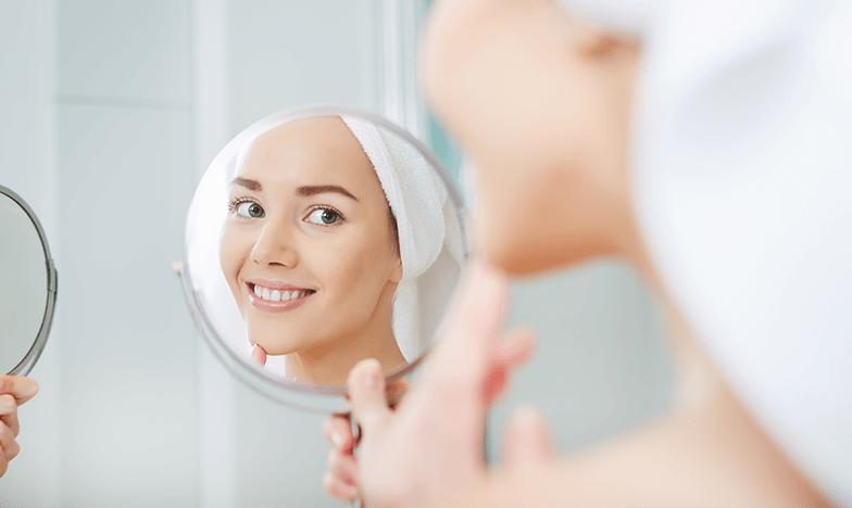 Красива жена, която се гледа в огледало