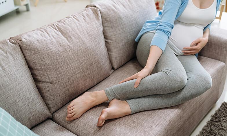 Бременна жена, която седи на дивана и страда от разширени вени