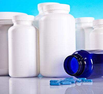 Шишенца за лекарства с няколко разпръснти таблетки до тях