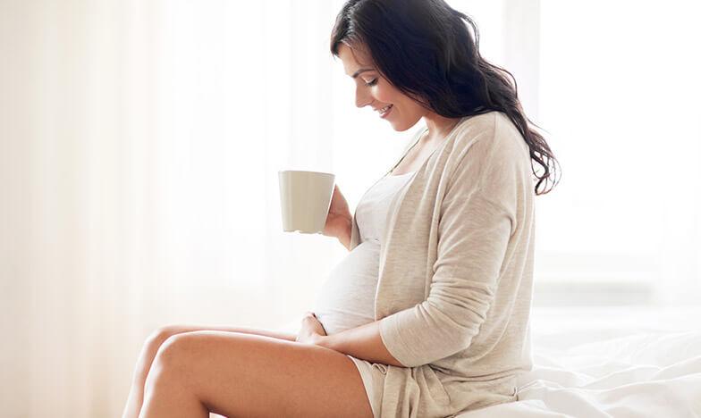 Бременна жена държи чаша и се гали по корема
