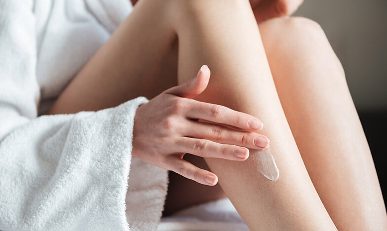 Жена нанася Шуслеров крем на краката си