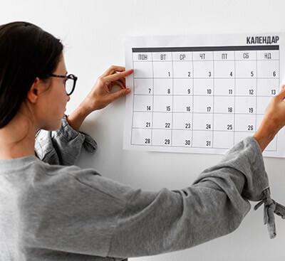Млада жена, която държи календар на стената