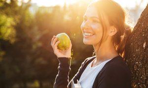 Красива жена яде ябълка подпряна на дърво