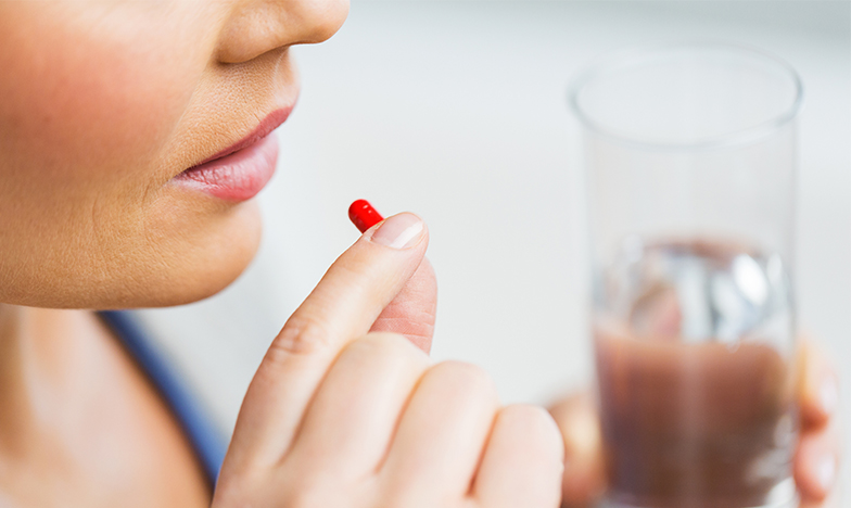 Жена пие лекарства с чаша вода