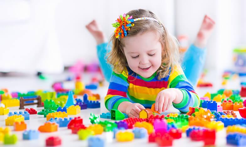 Момиченце си играе с играчки на пода