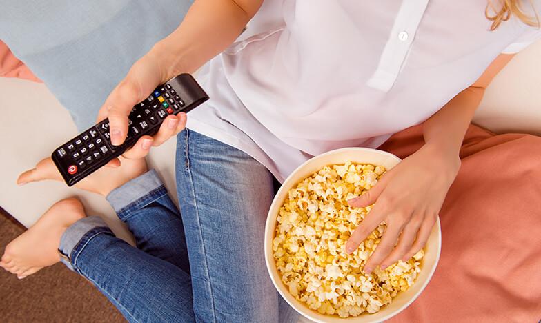 Жена, която гледа телевизия и яде пуканки