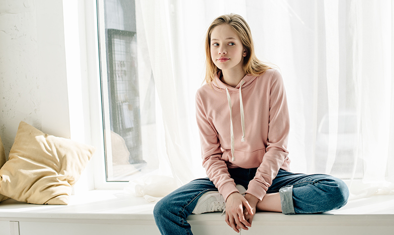 Момиче тийнейджър седи до прозорец