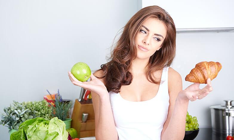 Жена държи ябълка и кроасан