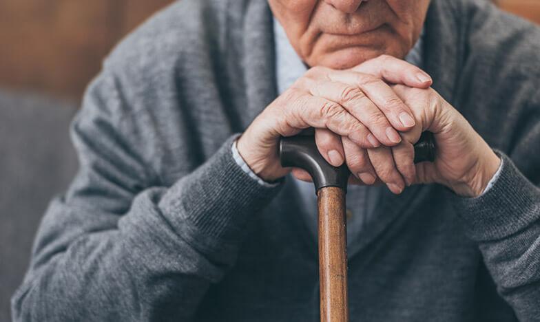 Възрастен мъж е подпрял брадичка на бастуна си