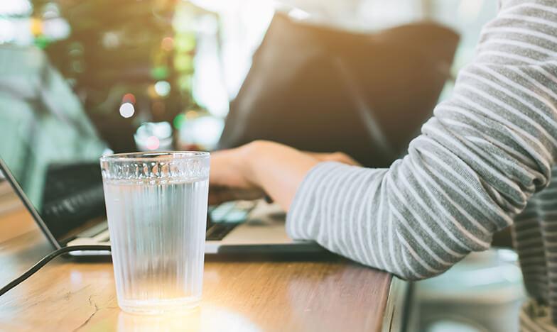 Жена пише на компютър, а до нея има чаша с вода
