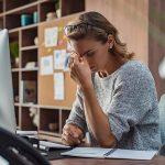 Жена се държи за главата, докато работи на бюрото