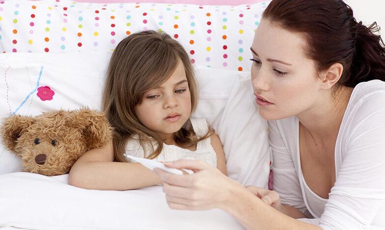 Mайка гледа температурата на детето