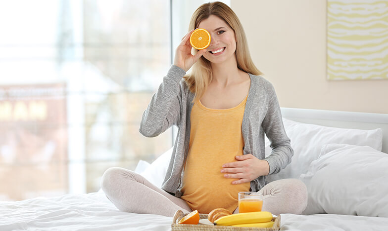бременна жена върху легло с плодове до нея