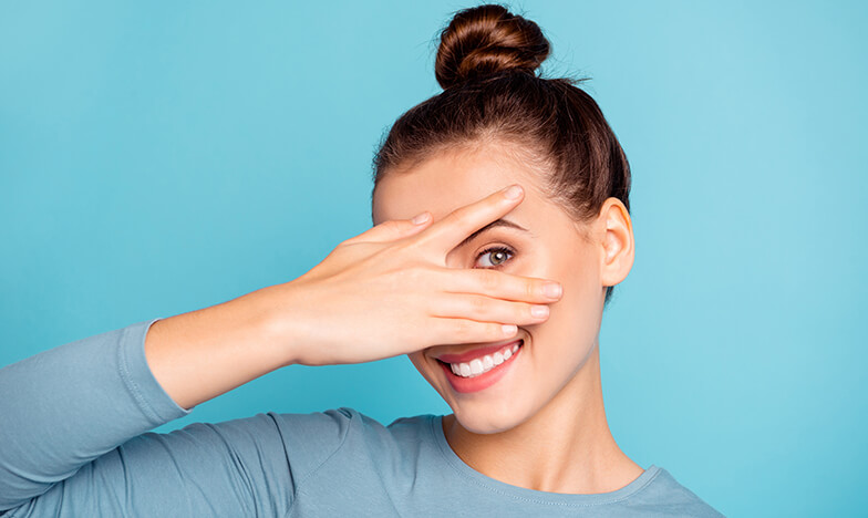 Момиче крие лицето си с ръка