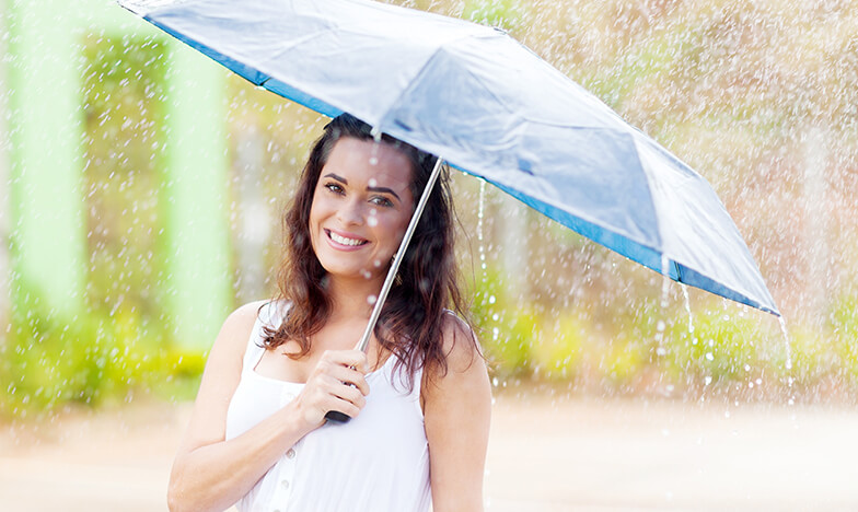Жена се радва на пролетния дъжд, който пречиства въздуха от алергени