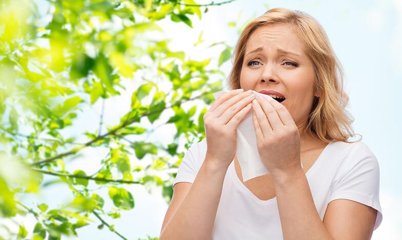 Жена със сенна хрема, която предизвиква кихане