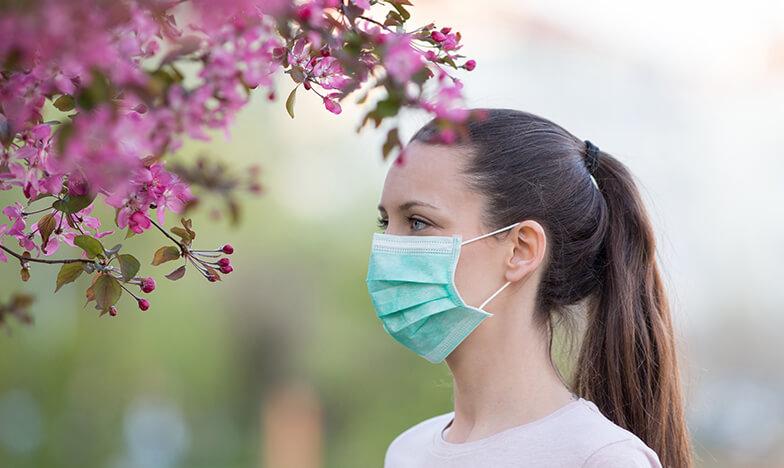 Жена носи маска през пролетта, за да се предпази от алергия