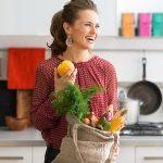 Щастлива жена в кухнята с покупки
