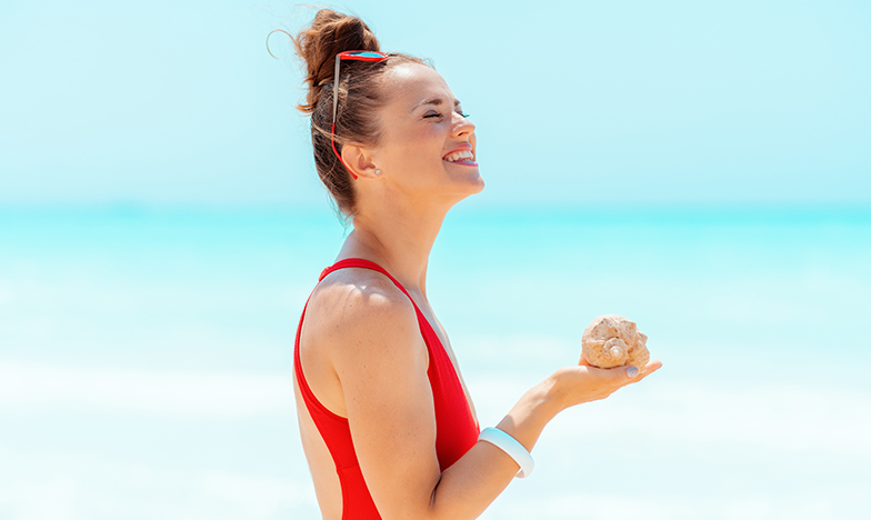 Младо, усмихнато момиче на плажа