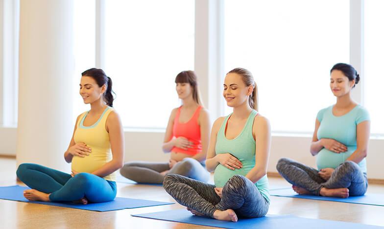 Жени практикуват йога по време на бременност